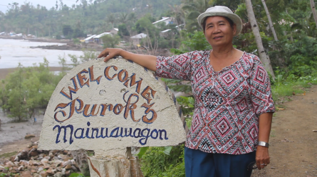 Ruth in front of her village welcome sign